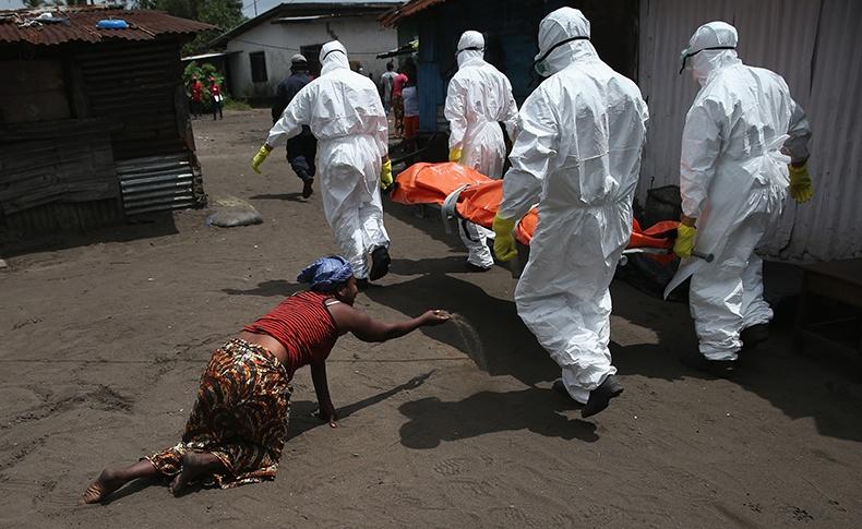 当地时间2014年10月10日,利比里亚首都蒙罗维亚,运尸队将感染埃博拉死亡的尸体运去火化,亲人悲痛欲绝。在利比里亚,火化尸体不符合当地传统文化 图片来源:视觉中国.jpg