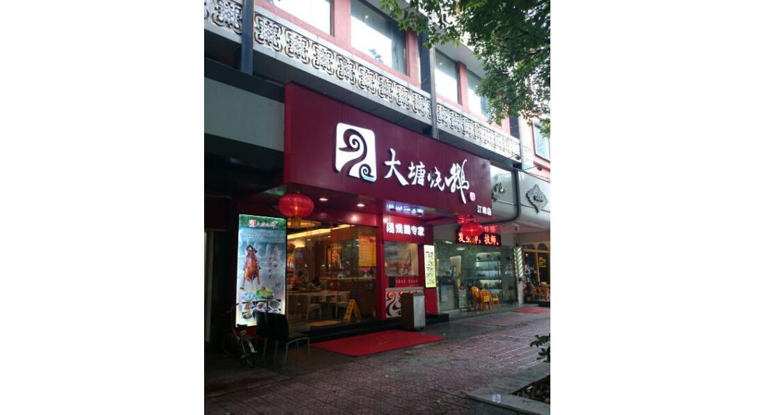 街道上有店铺的标志红色背景白色的字  中度可信度描述已自动生成