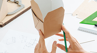 Box maker holding square food container in her fingers