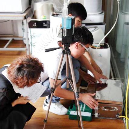 ▲实验人员正在操作开启气态污染物发生器(银色方盒)释放甲醛