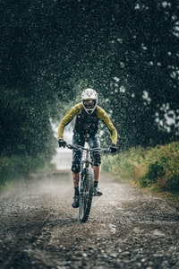 man in black jacket riding bicycle on road during daytime 白天穿着黑色夹克的男子在路上骑自行车