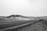 black asphalt road in the middle of snow covered field 黑色沥青路面在积雪覆盖的田野中间