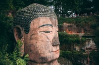 brown concrete statue near green plants during daytime 白天绿色植物附近的褐混凝土雕像