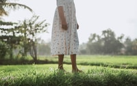 woman in white and pink floral dress standing on green grass field during daytime 白天,穿白色和粉色花裙的女人站在绿草地上。