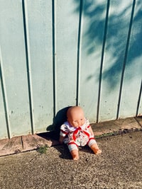 baby in white and red shirt and pants sitting on brown dirt 婴儿穿着白色和红色的衬衫和裤子坐在棕色的泥土上