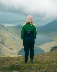 woman in green jacket standing on top of mountain during daytime 白天穿绿色夹克站在山顶上的女人