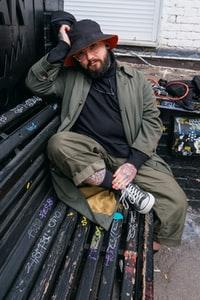 man in green jacket sitting on black wooden bench 身穿绿色夹克的男子坐在黑色木凳上