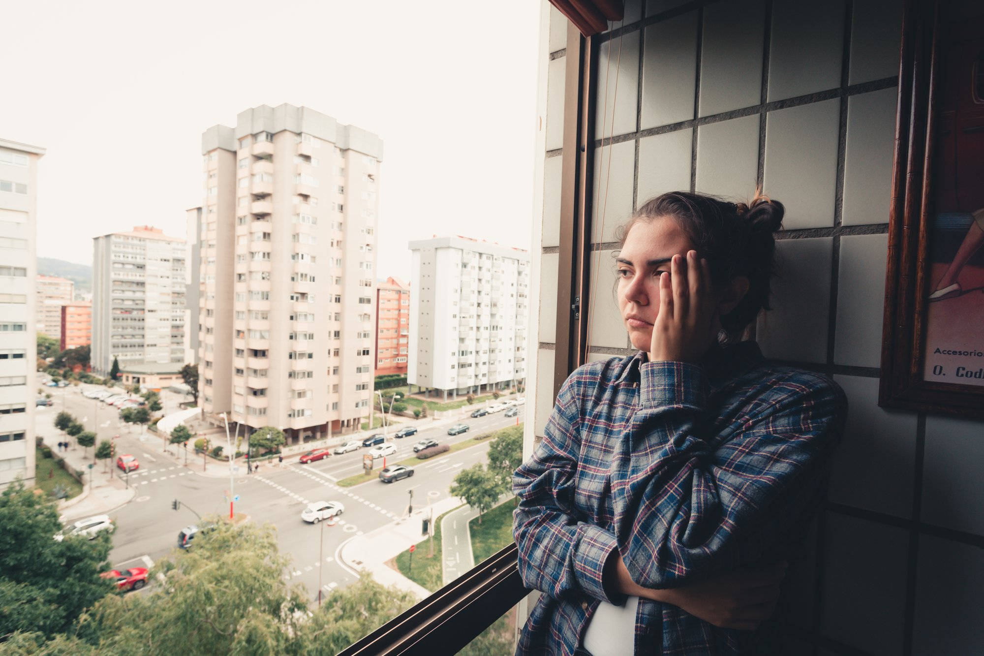 person standing by a window with their hand to their head 站在窗前用手抵着头的人