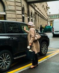 man in brown coat and black hat standing beside black suv during daytime 白天,身穿棕色外套,戴着黑色帽子的男子站在黑色SUV旁边。