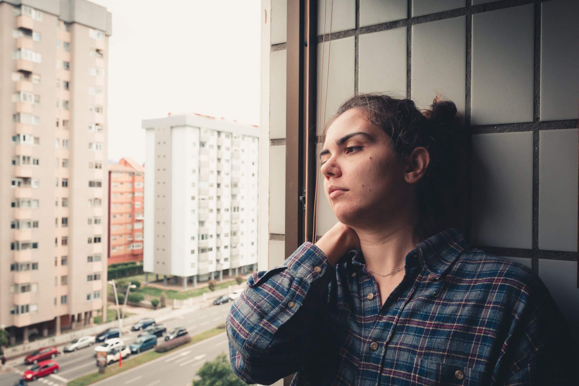 woman leans on a tiled wall and looks out the window 女人靠在铺着瓷砖的墙上望着窗外。
