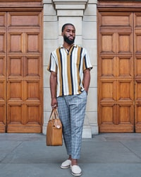 man in white and black striped polo shirt and gray pants standing on gray concrete floor 身穿白色和黑色条纹马球衫和灰色裤子的男子站在灰色混凝土地板上