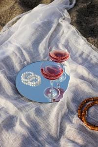 clear wine glass on blue and white round ceramic plate 蓝色和白色圆形陶瓷板上的透明酒杯