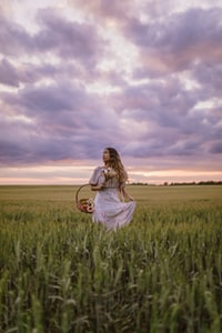 woman in white dress sitting on green grass field under cloudy sky during daytime 白衣女人白天坐在多云的草地上