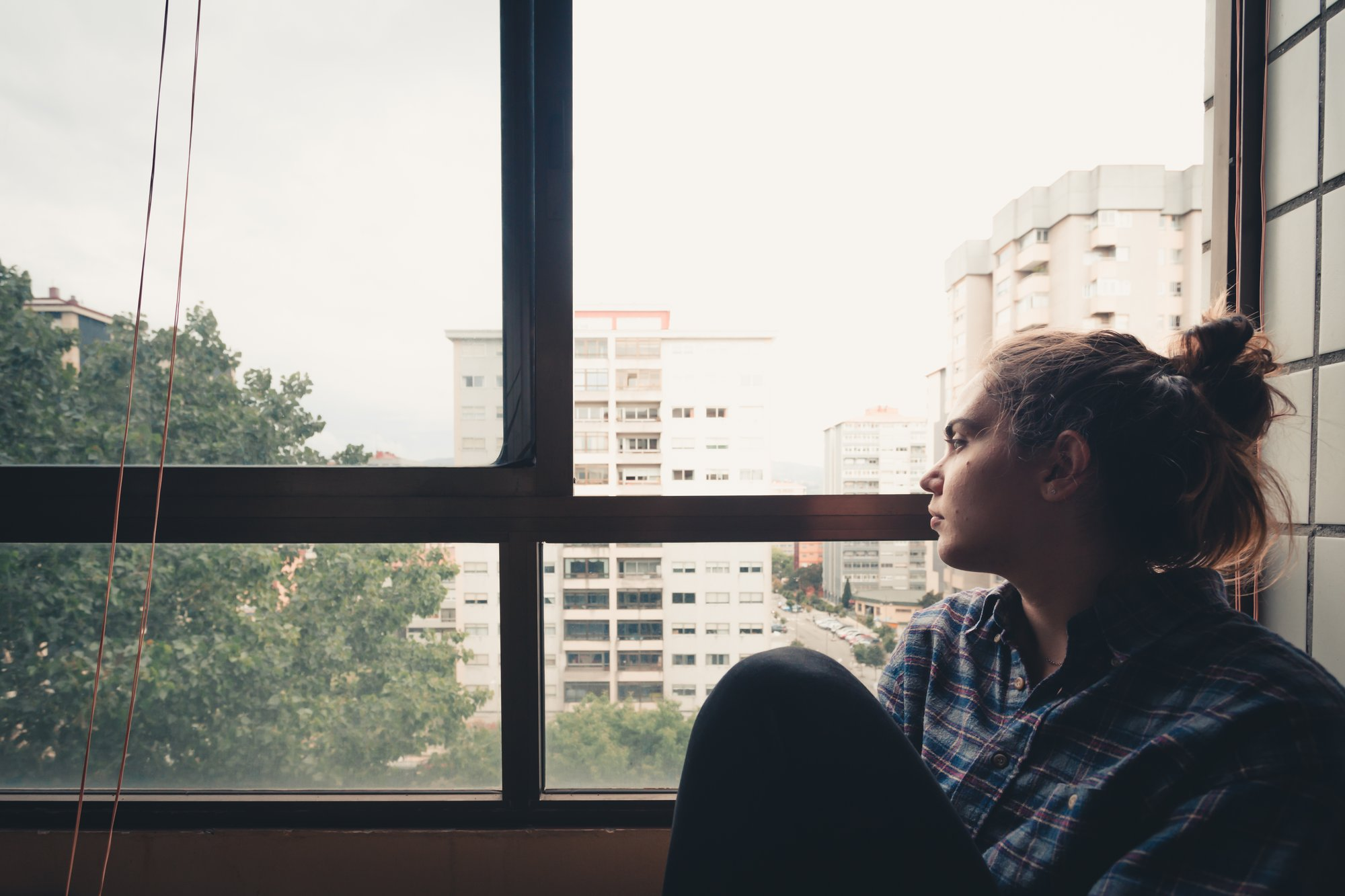 woman looks out a window to the view below 女人向窗外眺望下面的景色