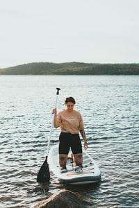 man in brown crew neck t-shirt and black shorts standing on white boat during daytime 白天身穿棕色船员领t恤和黑色短裤的男子站在白船上。