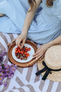 person holding brown round woven basket with red and orange fruits 拿着棕色圆形编织篮,红色和橙色水果的人