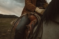 woman in brown leather jacket riding white horse during daytime 白天穿棕色皮夹克骑白马的女人