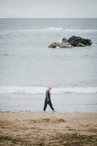 woman in black and white dress walking on beach during daytime 白天穿着黑白连衣裙在海滩上散步的女人