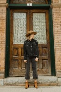 woman in black leather jacket and brown hat standing in front of brown wooden door 身穿黑色皮夹克和棕色帽子的女子站在棕色木门前