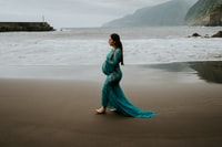 woman in blue dress standing on beach during daytime 白天穿着蓝色连衣裙站在海滩上的女人