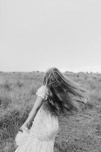 grayscale photo of woman in dress standing on grass field 穿衣服站在草地上的女人的灰阶照片