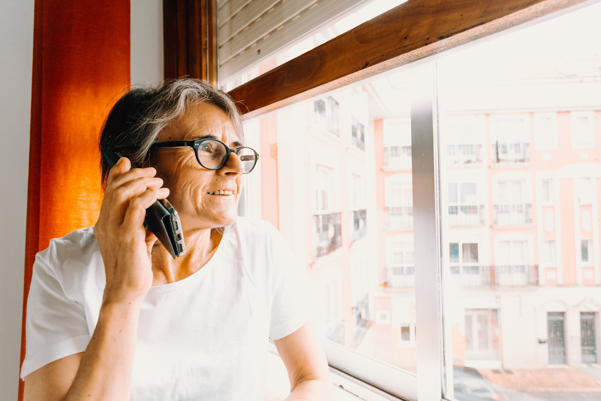 woman in glasses on the phone while looking out a window 戴眼镜的女人一边看窗外一边打电话
