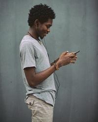 man in white crew neck t-shirt holding smartphone 身穿白色船员脖子的男子手持智能手机
