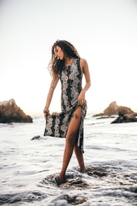 woman in black and white floral sleeveless dress standing on beach during daytime 白天穿着黑白无袖连衣裙站在海滩上的女人