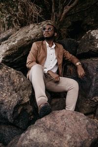 man in brown blazer and white dress shirt sitting on rock 穿棕色上衣和白色连衣裙坐在岩石上的男人