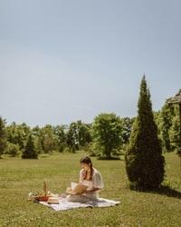 woman in white dress sitting on green grass field during daytime 白天穿着白色连衣裙坐在绿草地上的女人
