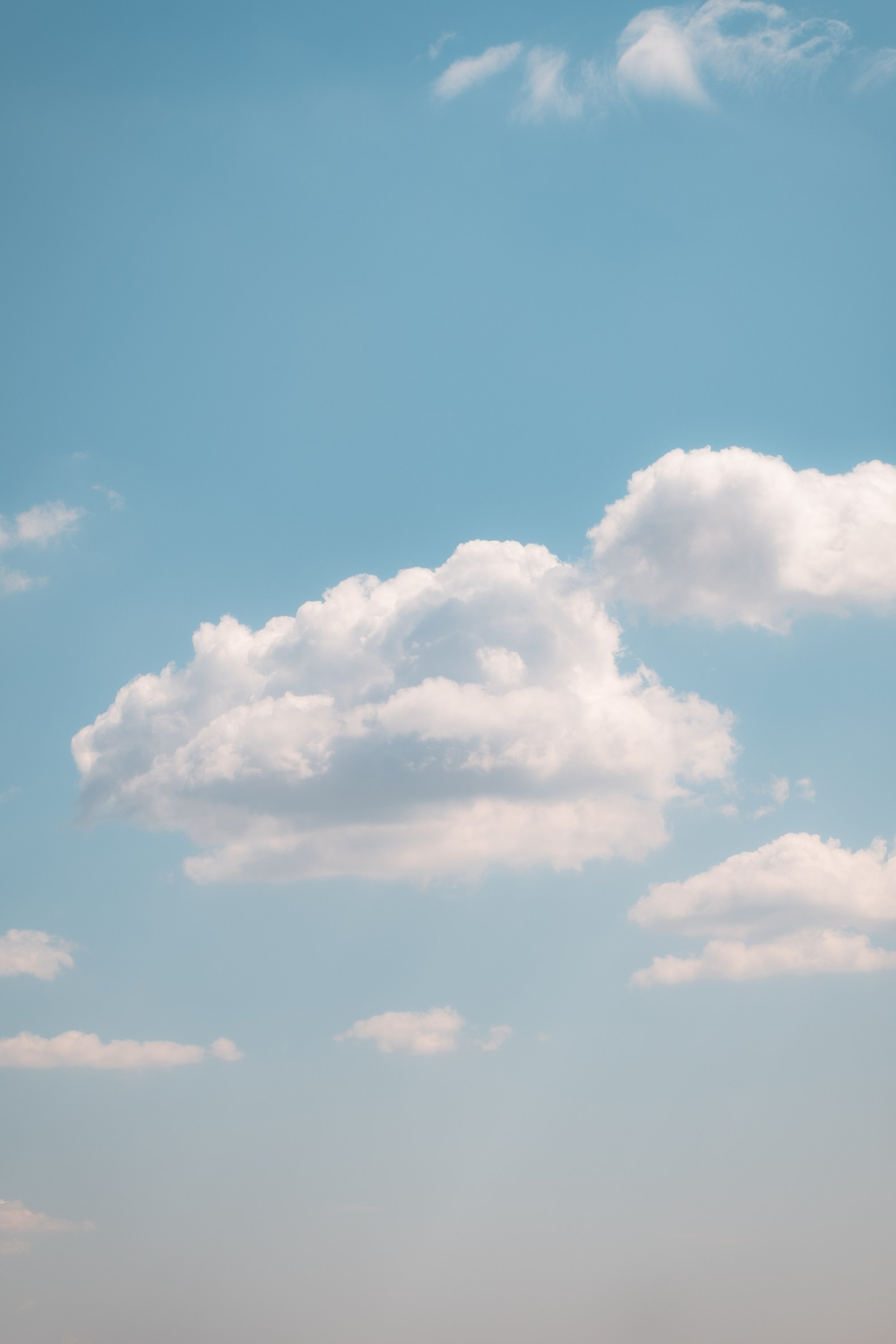 fluffy clouds in a light blue sky on a clear summer day 在晴朗的夏日,淡蓝色天空中的蓬松云