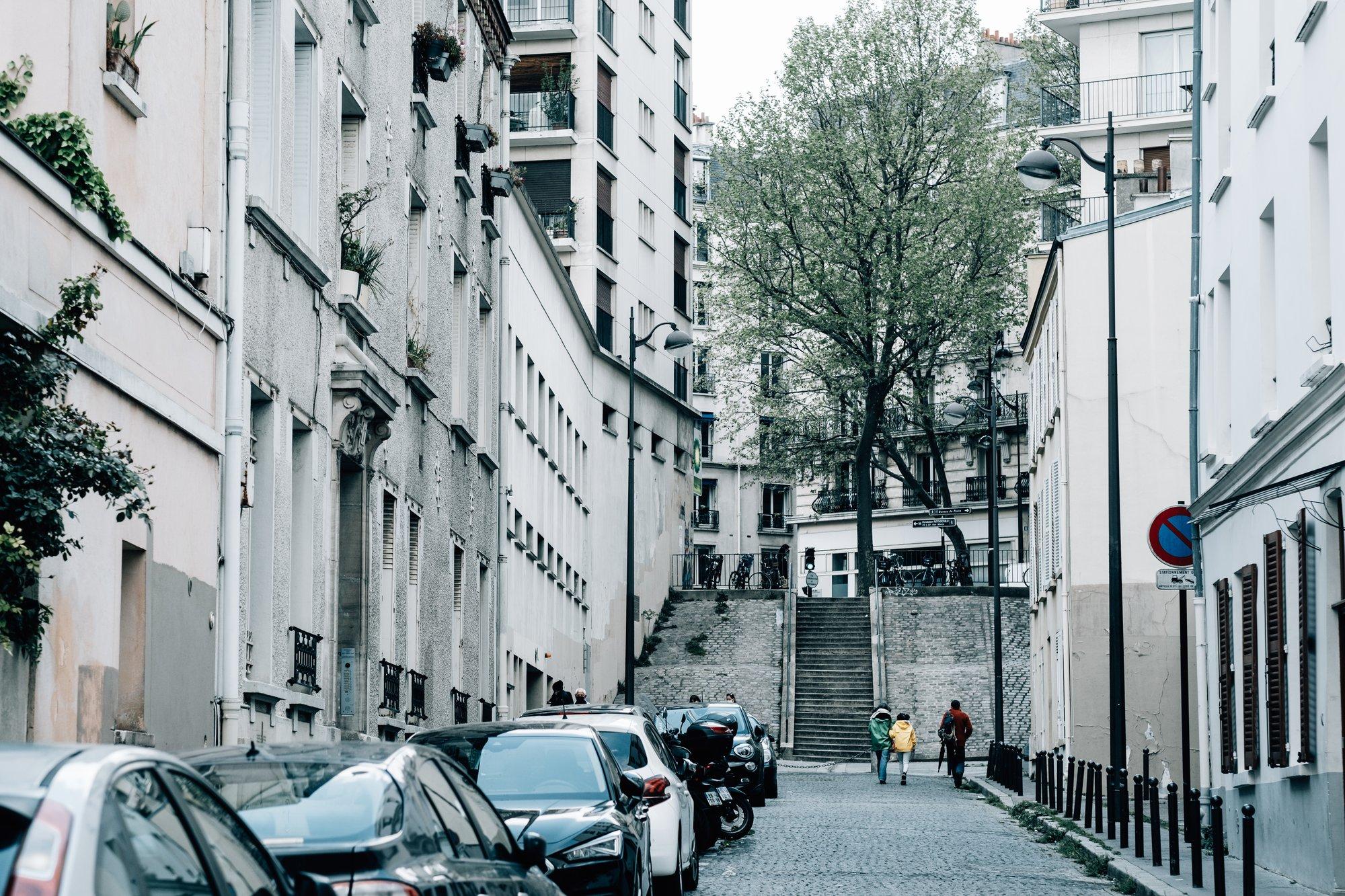 city street with cars and three pedestrians 有汽车和三个行人的城市街道