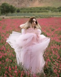 woman in white dress sitting on red flower field during daytime 白衣女人白天坐在红花坛上