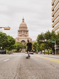 man riding bicycle on road near brown concrete building during daytime 白天,男子在棕色混凝土建筑物附近的道路上骑自行车。