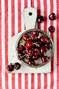 red cherries on brown ceramic bowl 棕色陶瓷碗上的红色樱桃