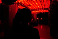 silhouette of woman standing near red and yellow string lights during night time 夜间站在红灯和黄灯旁的女人的轮廓
