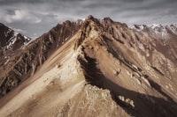 brown rocky mountain under blue sky during daytime 白天蓝天下褐色的岩石山