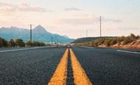 gray concrete road between green grass field during daytime 白天绿草场之间的灰色混凝土路