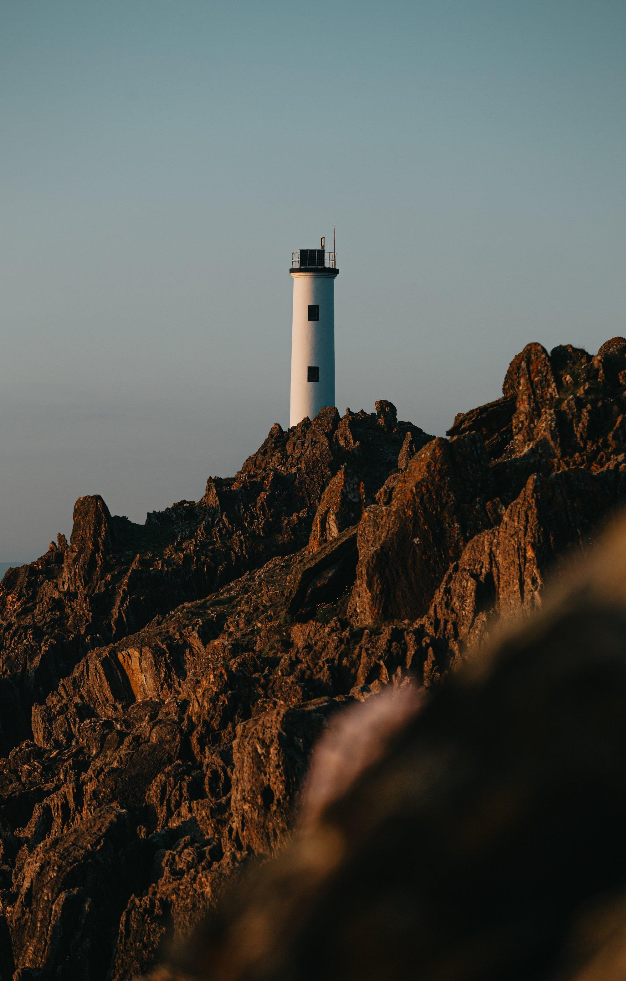 a lighthouse sits on top of a sharp mountain ridge 一座灯塔坐落在一座陡峭的山脊上。