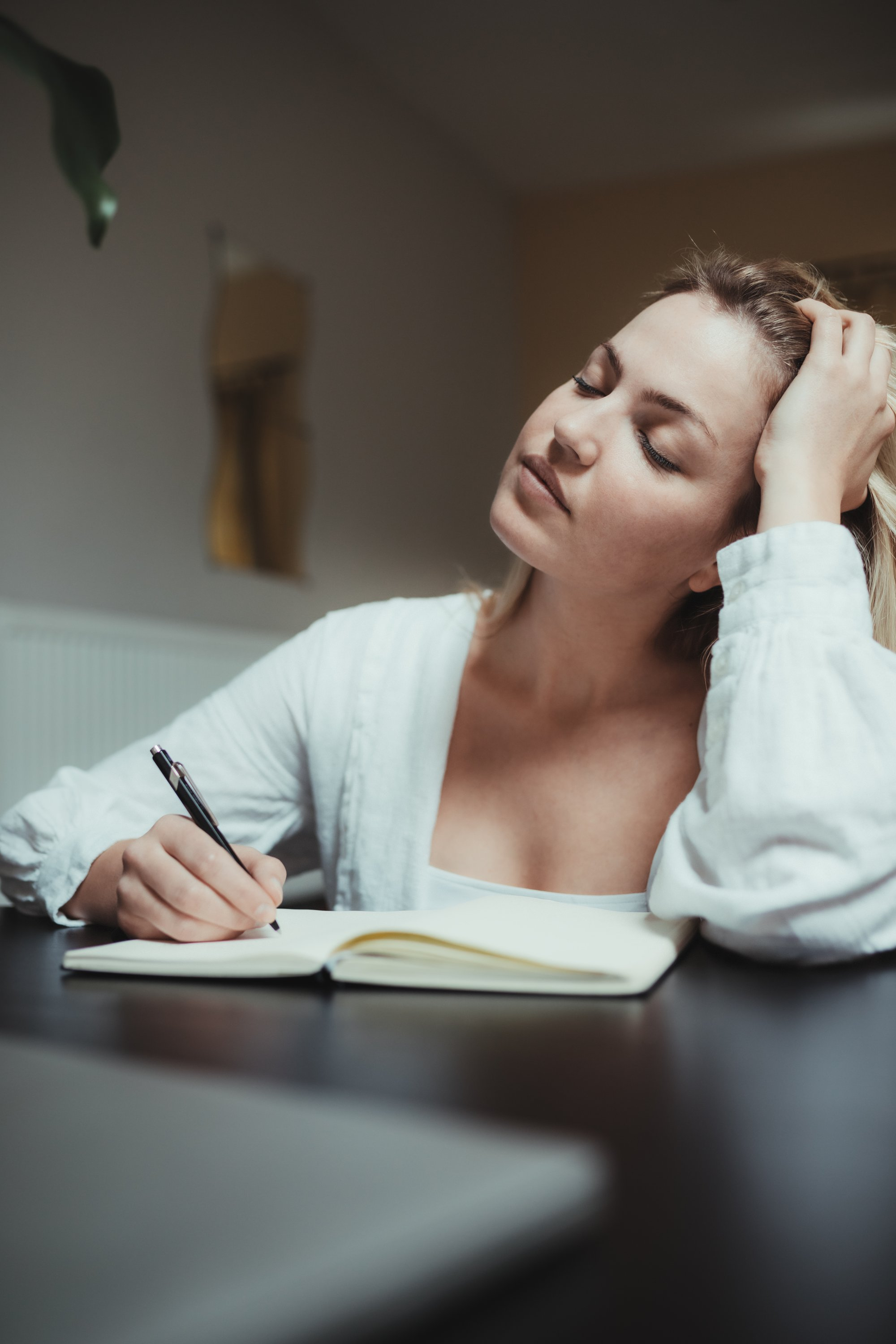 woman holds her head thinking while writing in a journal 在日记里写作时,女人抱着头思考。