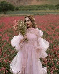 woman in pink dress holding bouquet of flowers 穿着粉色连衣裙的女人拿着一束花