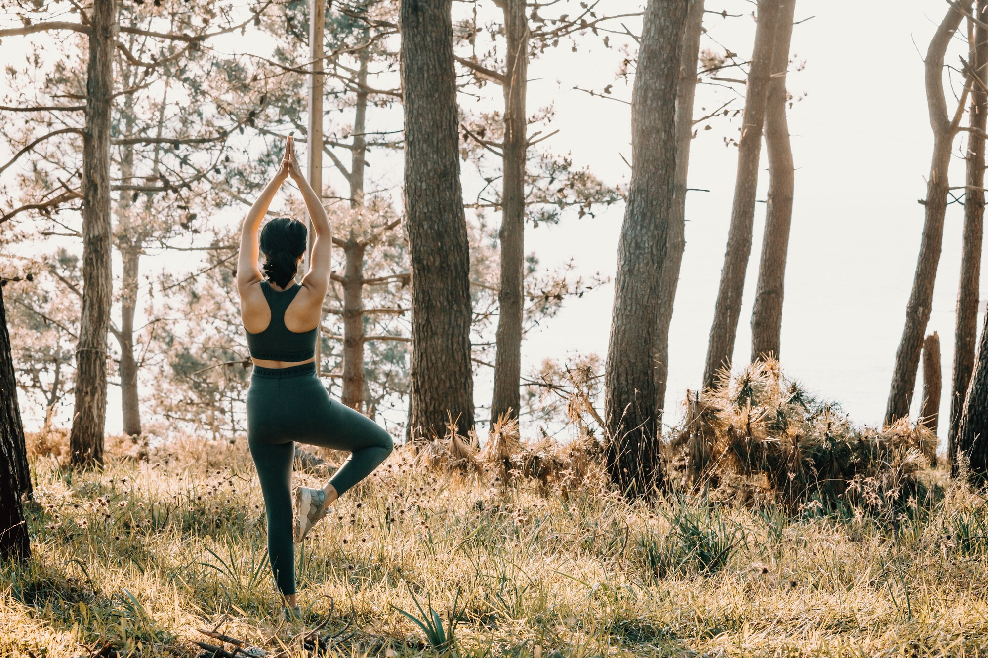 person with arms reaching high does yoga in a forest 双臂高举的人在森林里做瑜伽。
