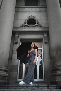 woman in black and white stripe dress covering her face with black umbrella standing on gray