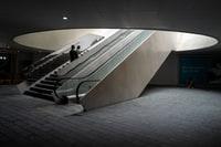 man in black jacket walking on gray concrete stairs