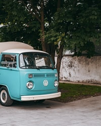 blue and white volkswagen t-2 parked beside white concrete wall during daytime