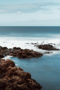 brown rocky shore with blue ocean water during daytime