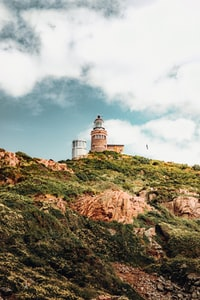 white lighthouse on brown hill under white clouds and blue sky during daytime