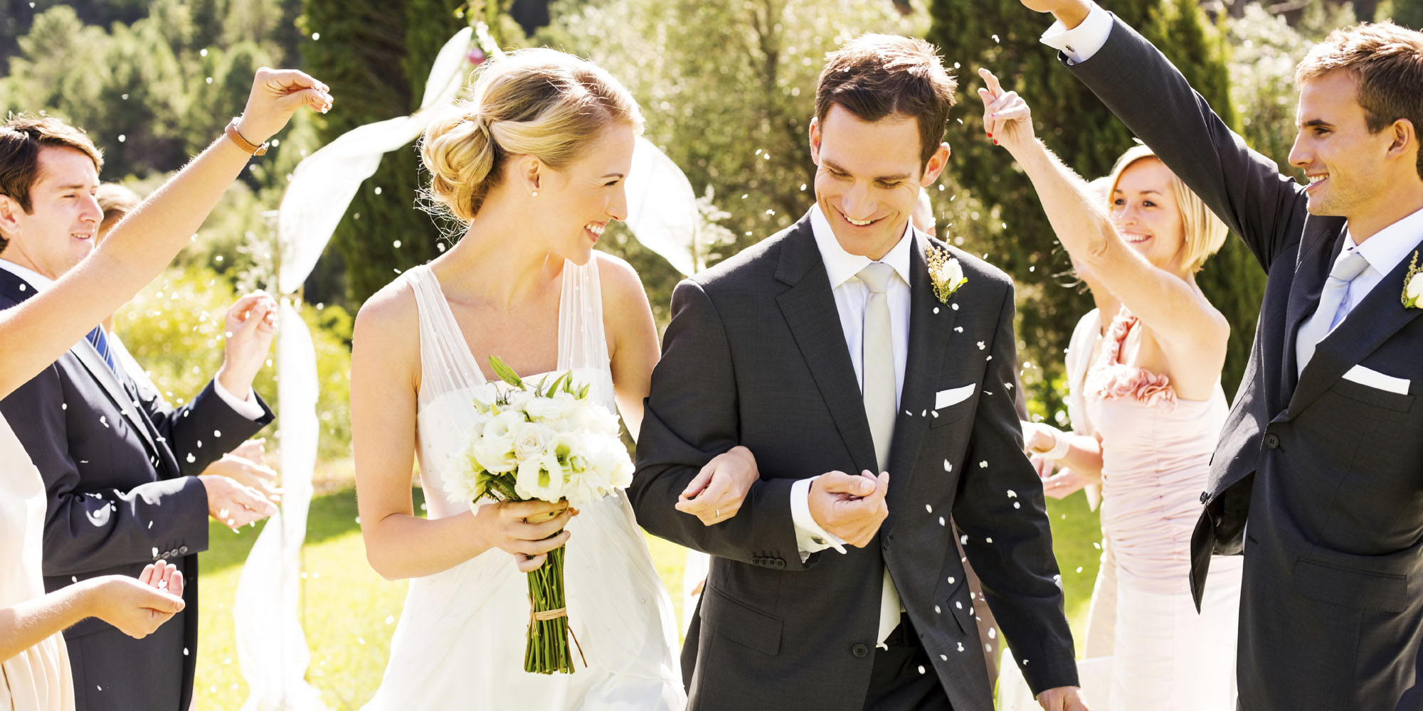 Couple Walking While Guests Throwing Confetti On Them