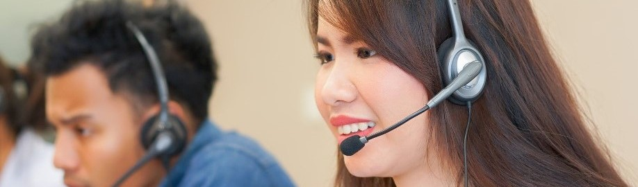 close up on asian call center woman work with diverse ethnic employee at operation monitor room for contact or talking with customer concept_edited