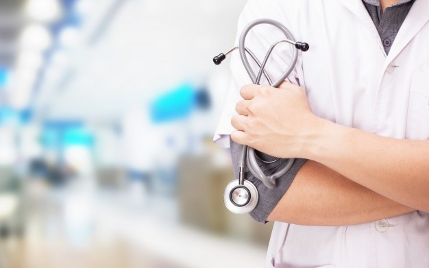 doctor-with-stethoscope-hands-hospital-background_1423-1